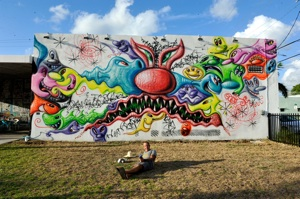 Kenny Scharf poses in front of his expanded mural, as part of Wynwood Walls. Photo by Martha Cooper